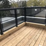patio railing with black aluminum handrail and glass in toronto
