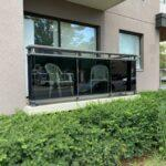 aluminum railing on a ground level balcony with super grey glass